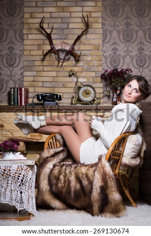 Sexy woman in white socks and sweater posing on the chair - stock photo