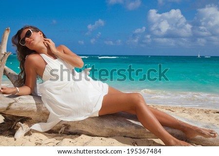 Sexy woman in white summer dress enjoying nature on the exotic beach. Beauty girl outdoor. Freedom concept. - stock photo
