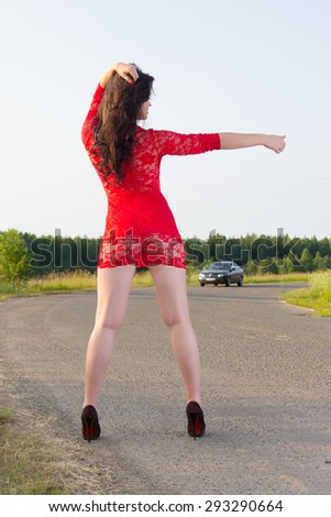 Sexy woman  is catching a car hitchhiking - stock photo