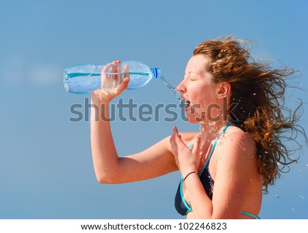 sexy woman is refreshing herself with bottle of water