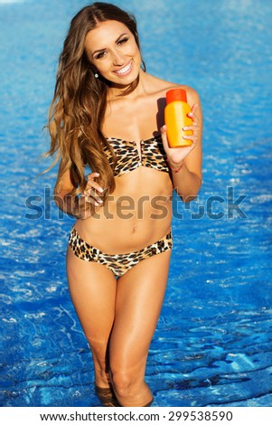 Sexy woman is resting near swimming pool with blue water, summer time