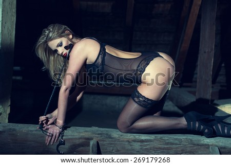 Sexy woman kneeling on the timber in barn at night, sensuality and bdsm - stock photo