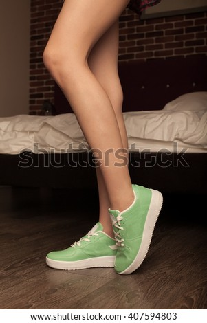 Sexy woman leg in green Sneakers shoes walking on Dirty wooden