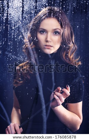Sexy woman looks out the window holding a riding crop in her hands