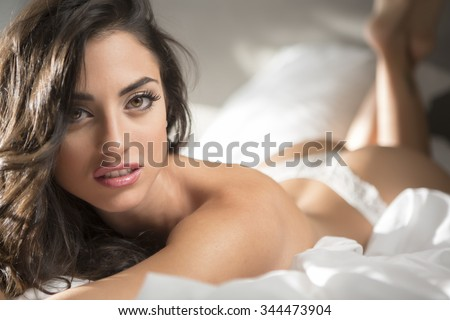 Sexy woman lying down on the bed - stock photo