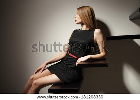 sexy woman lying on stairs over grey bakground