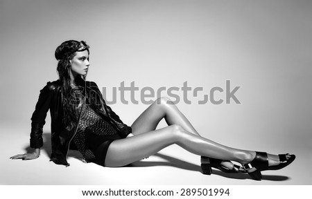 sexy woman model dressed punk, wet look, posing in the studio - stock photo