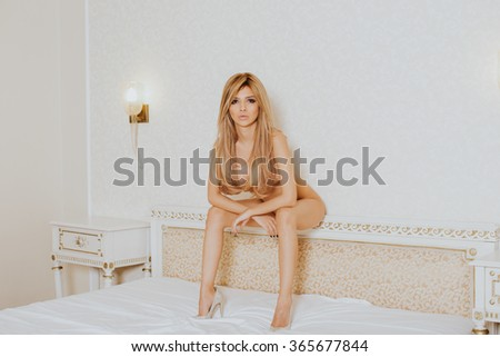 Sexy woman nude in posing in her bed - stock photo