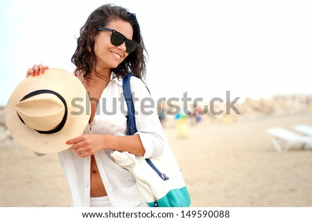 Sexy woman on beach smiling and enjoying a sunny, relaxing day at resort - stock photo