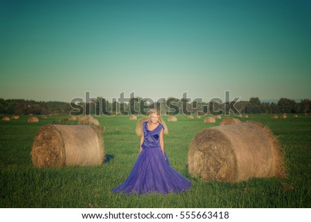 Sexy woman on hay stack on sunset.