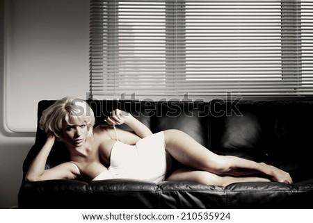 sexy woman on leather sofa - stock photo
