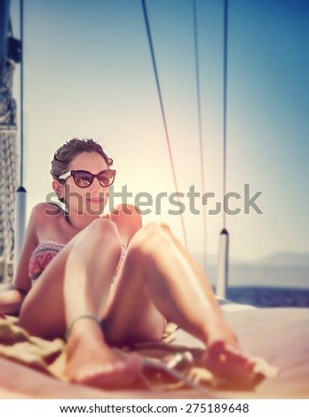 Sexy woman on sailboat lying down on the deck of luxury sailboat, tanning on bright sun light, enjoying sea cruise, active summer holidays and vacation - stock photo