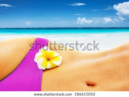 Sexy woman on the beach, body part, wearing stylish pink bikini, yellow frangipani flower on the belly, healthy lifestyle, summer vacation concept