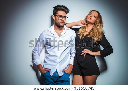sexy woman pose in studio close to a man with hands in pockets while looking away