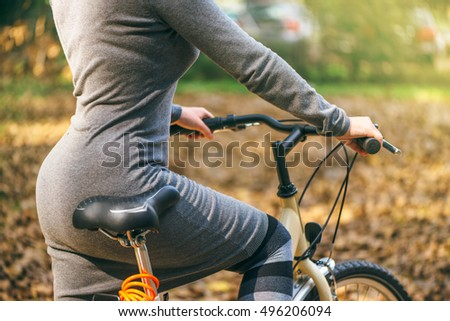 Sexy woman poses with her bicycle in park during autumn. Unrecognizable attractive young adult female with vintage retro bike, cycling or commuting, ecological transportation concept.
