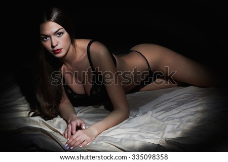 sexy woman posing in black lingerie in bed. Hot woman with perfect slim body.Lady lying in bed - stock photo