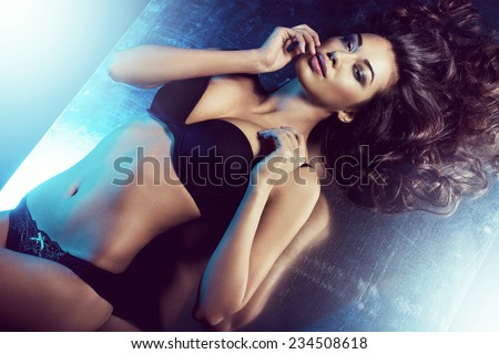 sexy woman posing in black sensual lingerie with blue light coming from behind. Fashion shot - stock photo
