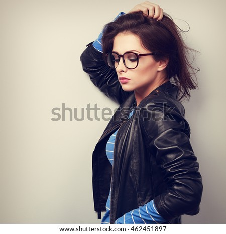 Sexy woman posing in fashion black leather jacket and eye glasses. Toned portrait