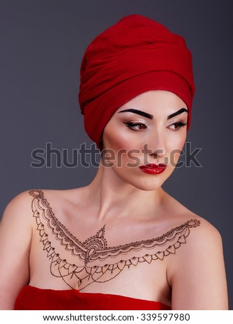 sexy woman posing in the studio, red lips, isolated violet blue background, henna tattoo on chest - stock photo