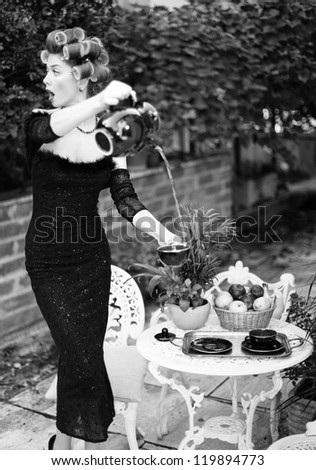 sexy woman pouring tea funny concept - fashion shoot (intentional soft focus and vintage look)