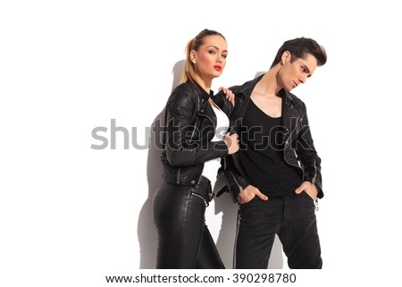 sexy woman pulling her lover by his leather jacket and looks to the camera while he looks away - stock photo