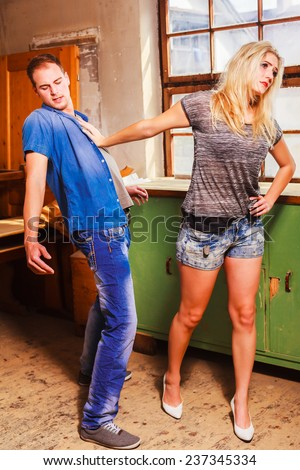 Sexy woman rejecting a mans advances pushing him away with her hand with a look of disdain. / Sexy woman rejecting a mans advances - stock photo