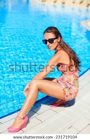 Sexy Woman relaxing at the pool - stock photo