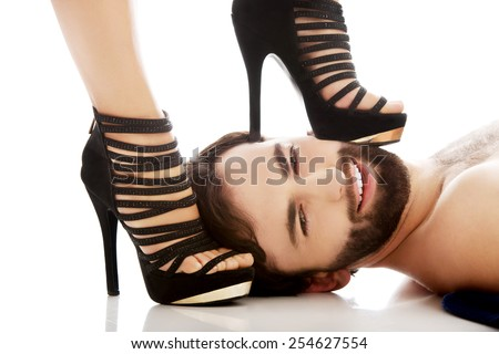 Sexy woman's foot in high heel on man's face, dominating him. - stock photo