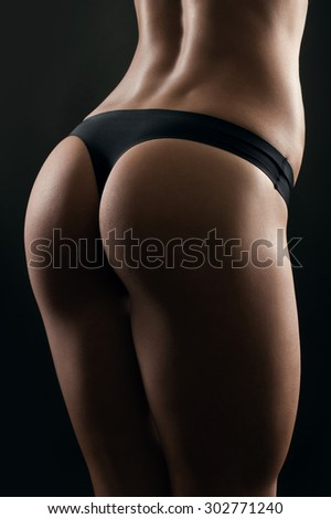Sexy woman's sport buttocks in black lingerie close-up - stock photo