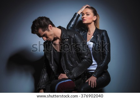 sexy woman seated behind her man, posing in studio while resting her arm on his back. the man is looking down.  - stock photo