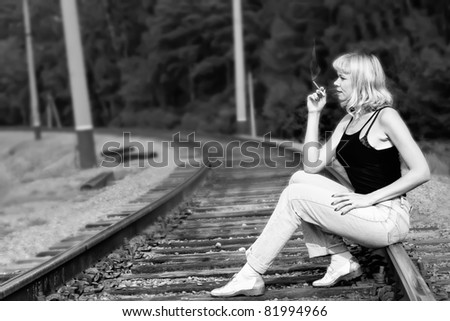 Sexy woman seating on railway and smoking cigarette - stock photo