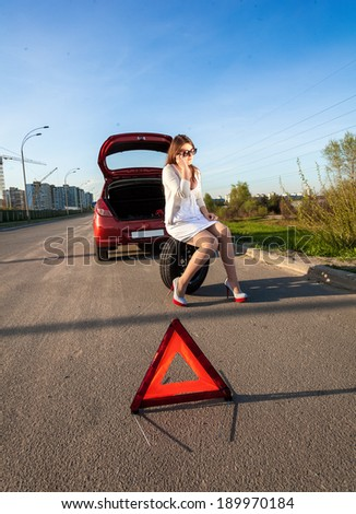 Sexy woman sitting on spare wheel against of broken car and warning sign - stock photo