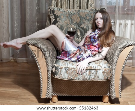 Sexy woman sitting on the armchair at home - stock photo