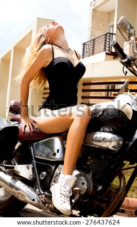 Sexy woman sitting on the chopper and enjoy the ride,dressed in sexy black bodysuit.Lifestyle portrait bright toned colors,cool rock n roll girl,Enjoy ride in summer sunny hot days,red lips,passion - stock photo