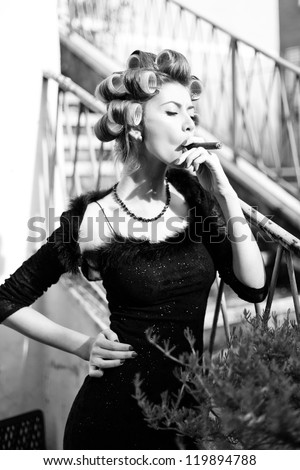 sexy woman smoking a Cuban cigar - fashion shoot (intentional soft focus and vintage look) - stock photo