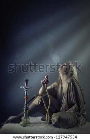 sexy woman smoking the hookah - stock photo
