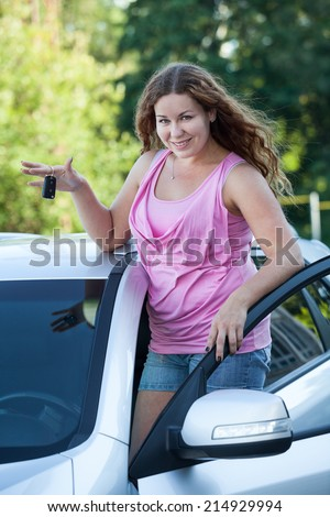 Sexy woman standing over car roof with ignition key - stock photo
