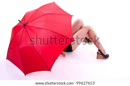 Sexy woman standing under red umbrella on white background