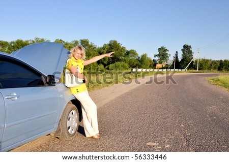 sexy woman stopping car on the road near broken auto - stock photo