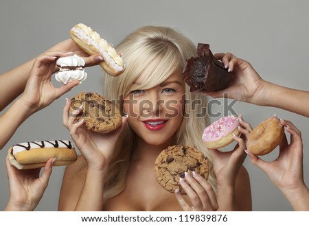 sexy woman surrounded  by many hands holding cream cakes with so much choice and temptation is she going to forget about her diet and indulge herself