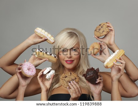 sexy woman surrounded  by many hands holding cream cakes with so much choice and temptation is she going to forget about her diet and indulge herself - stock photo