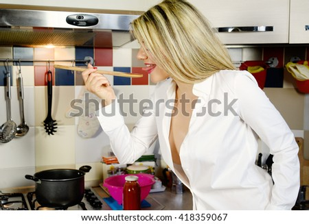 sexy woman tasting red tomato sauce in a kitchen
