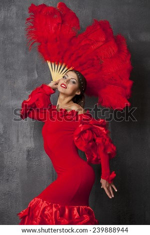 Sexy Woman traditional Spanish Flamenco dancer dancing in a red dress with fan  - stock photo