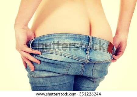 Sexy woman undressing her jeans trousers.