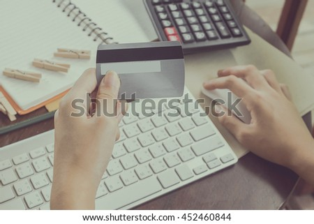 Sexy woman using computer to online shopping and pay by credit card, Low light, selective focus on hand, can be used for e-commerce, business, technology and internet concept, Vintage tone filter