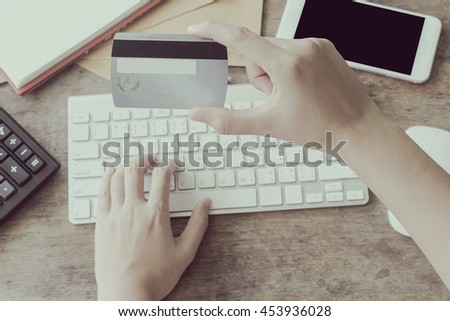 sexy woman using computer to online shopping and pay by credit card, Low light, selective focus on hand, can be used for e-commerce, business, technology and internet concept, Vintage tone filter - stock photo