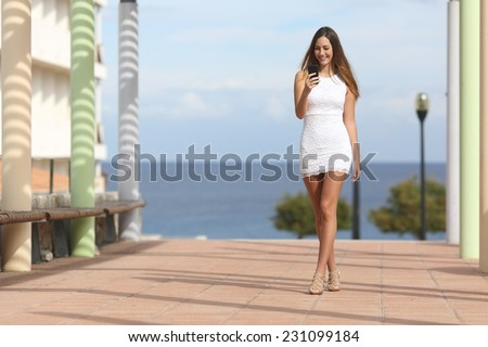 Sexy woman walking and texting on the smart phone in a street near the beach with the sea in the background - stock photo