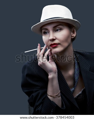 sexy woman wearing a suit and a hat, against red studio background