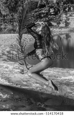 Sexy woman wearing black swimsuit sitting on the tree branch with artistic shadow pattern on body and face while holding palm tree leaf over small sea lake background - black and white photo