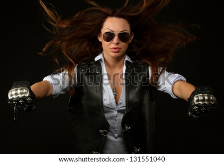 Sexy woman wearing leather jacket and sunglasses (riding on an invisible bike) - stock photo